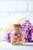 Βάζο γυαλιού με το πετρέλαιο αρώματος και με τα ιώδη λουλούδια για τη SPA και aromatherapy Έννοια SPA Στοκ εικόνα με δικαίωμα ελεύθερης χρήσης