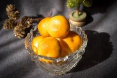 Βάζο κρυστάλλου με tangerine στο γκρίζο υπόβαθρο στοκ εικόνα με δικαίωμα ελεύθερης χρήσης