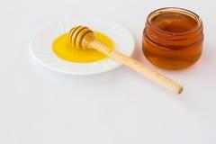 Βάζο με ένα σκοτεινό μέλι Dipper μελιού σε ένα άσπρο πιατάκι με ένα λι Στοκ Εικόνα