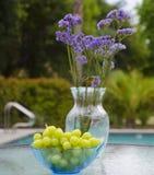 Βάζο με τα λουλούδια και τα σταφύλια από τη λίμνη Στοκ Εικόνα