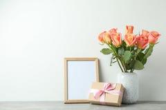 Βάζο με τα τριαντάφυλλα, το δώρο και το κενό πλαίσιο στον γκρίζο πίνακα στοκ εικόνες με δικαίωμα ελεύθερης χρήσης