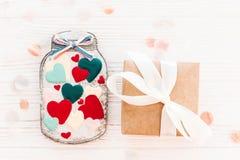 Βάζο με τις ζωηρόχρωμες καρδιές μπισκότων και κιβώτιο δώρων τεχνών στην άσπρη σκουριά Στοκ Εικόνα