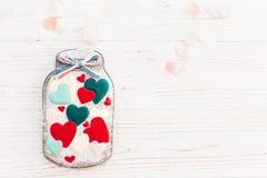 Βάζο με τις ζωηρόχρωμες καρδιές μπισκότων με το κομφετί στο άσπρο αγροτικό wo Στοκ Εικόνες