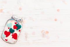 Βάζο με τις ζωηρόχρωμες καρδιές μπισκότων με το κομφετί στο άσπρο αγροτικό wo Στοκ εικόνες με δικαίωμα ελεύθερης χρήσης