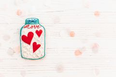 Βάζο με τις ζωηρόχρωμες καρδιές μπισκότων με το κομφετί στο άσπρο αγροτικό wo Στοκ Φωτογραφίες