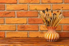 Βάζο με τις καλλιτεχνικές βούρτσες στο υπόβαθρο του παλαιού τούβλινου wa Στοκ Φωτογραφία