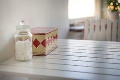 Βάζο με τους κύβους άσπρης ζάχαρης και εκλεκτής ποιότητας κιβώτιο στον πίνακα Στοκ Εικόνα