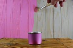 Βάζο με το ρόδινο διαθέσιμο ξύλινο υπόβαθρο χρωμάτων και χρωμάτων χεριών βουρτσών Στοκ φωτογραφία με δικαίωμα ελεύθερης χρήσης