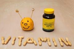 Βάζο συμπληρωμάτων και ένα σημάδι βιταμινών που δημιουργείται από τα χάπια βιταμινών Στοκ Εικόνες