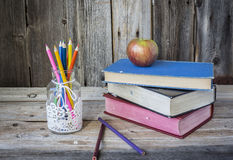 Βάζο των κραγιονιών μολυβιών με μια συνεδρίαση μήλων στα συσσωρευμένα βιβλία Στοκ εικόνα με δικαίωμα ελεύθερης χρήσης