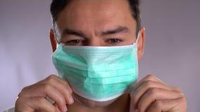 Βάλτε τη μάσκα, κλείστε επάνω το πορτρέτο ενός χειρούργου ή ενός γιατρού με τη μάσκα και μιας κάσκας έτοιμης για τη λειτουργία στ απόθεμα βίντεο