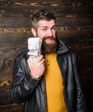 Βάναυσα γενειοφόρα σακάκι δέρματος ένδυσης hipster ατόμων και χρήματα μετρητών λαβής Παράνομο κέρδος και μαύρα μετρητά Έμπορος μα στοκ εικόνες