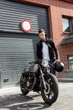 Βάναυσο άτομο κοντά στη μοτοσικλέτα συνήθειας δρομέων καφέδων του στοκ εικόνες