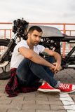 Βάναυσο άτομο κοντά στη μοτοσικλέτα συνήθειας δρομέων καφέδων του στοκ φωτογραφία