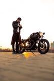 Βάναυσο άτομο κοντά στη μοτοσικλέτα συνήθειας δρομέων καφέδων του στοκ εικόνα