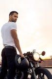 Βάναυσο άτομο κοντά στη μοτοσικλέτα συνήθειας δρομέων καφέδων του στοκ εικόνα με δικαίωμα ελεύθερης χρήσης