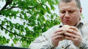 Βάναυσο μέσης ηλικίας άτομο για να φάει το γρήγορο φαγητό υπαίθρια απόθεμα βίντεο