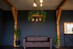 Βάναυσο σύγχρονο εσωτερικό σε ένα σκοτεινό χρώμα με έναν καναπέ δέρματος Καθιστικό ύφους σοφιτών στοκ εικόνα