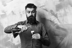 Βάναυσο hipster που κρατά τον οινοπνευματώδη πυροβολισμό και το σωλήνα ή τη φιάλη γυαλιού στοκ εικόνα με δικαίωμα ελεύθερης χρήσης