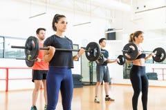 Βάρη ανύψωσης Bodybuilders στεμένος στη γυμναστική στοκ φωτογραφίες