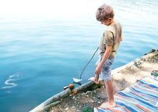 Βάρκα εγγράφου έναρξης αγοριών στο νερό λιμνών Στοκ Φωτογραφία
