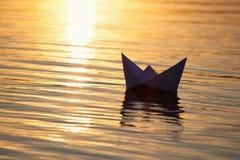Βάρκα εγγράφου που πλέει με το νερό με τα κύματα και τους κυματισμούς Στοκ Φωτογραφίες