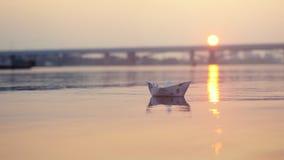 Βάρκα εγγράφου στο νερό κατά τη διάρκεια του όμορφου ηλιοβασιλέματος με τον ήλιο αντανάκλασης στη θάλασσα Στοκ εικόνα με δικαίωμα ελεύθερης χρήσης
