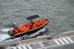 Βάρκα και υπάλληλος λιμενικής αρχής που ελέγχουν την περιοχή αποβαθρών στοκ εικόνα με δικαίωμα ελεύθερης χρήσης