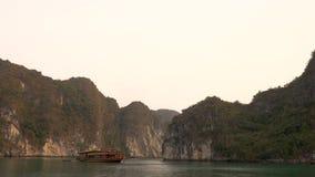 Βάρκα κρουαζιέρας που πλέει στο ηλιοβασίλεμα στο μακρύ κόλπο εκταρίου, Βιετνάμ απόθεμα βίντεο