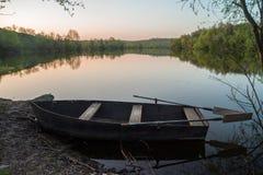 Βάρκα με τα κουπιά στην ακτή ποταμών στο ηλιοβασίλεμα στοκ φωτογραφίες