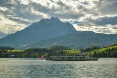 Βάρκα με τους τουρίστες στη λίμνη Λουκέρνη με την αιχμή Pilatus στο υπόβαθρο στοκ φωτογραφία με δικαίωμα ελεύθερης χρήσης