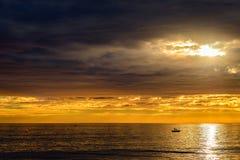 Βάρκα με τους ψαράδες στο ηλιοβασίλεμα στοκ εικόνες