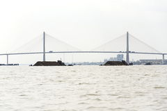 Βάρκα με το χώμα που επιπλέει Mekong με τη γέφυρα της Rach Mieu στις 14 Φεβρουαρίου 2012 στο Tho μου, Βιετνάμ Στοκ Εικόνες
