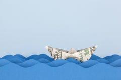 Βάρκα δολαρίων που κολυμπά στα κύματα εγγράφου Στοκ Φωτογραφία