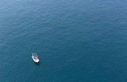 Βάρκα που επιπλέει στην ήρεμη μπλε θάλασσα Στοκ Φωτογραφία