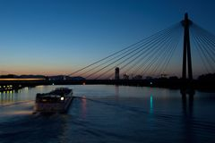 βάρκα που κινείται στα περάσματα ποταμών και τραίνων πέρα από τη γέφυρα, Βιέννη στοκ φωτογραφία