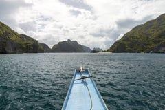 Βάρκα που πηγαίνει μεταξύ των πράσινων νησιών με τα δραματικά σύννεφα Στοκ Φωτογραφία
