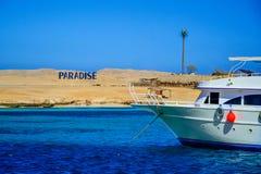 Βάρκα που πλέει με μια παραλία παραδείσου Στοκ Εικόνες