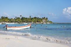 Βάρκα στην ακτή της καραϊβικών θάλασσας και των ανθρώπων που έχουν τη διασκέδαση στην παραλία σε Tulum, χερσόνησος Γιουκατάν, Μεξ στοκ φωτογραφίες
