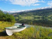 Βάρκα στην όμορφη σαφή λίμνη στη Νορβηγία Χιονώδη βουνά στην ανασκόπηση Στοκ Εικόνες