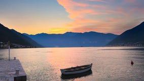 Βάρκα στη θάλασσα στο ηλιοβασίλεμα και το υπόβαθρο βουνών απόθεμα βίντεο