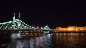 Βάρκα στον ποταμό Δούναβη κοντά στη γέφυρα ελευθερίας που φωτίζεται τη νύχτα απόθεμα βίντεο