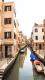 Βάρκα στο κανάλι της Βενετίας με το ζωηρόχρωμο κτήριο Στοκ Εικόνες