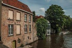 Βάρκα τουριστών και παλαιά κτήρια τούβλου στην άκρη καναλιών ` s σε μια ηλιόλουστη ημέρα στη Μπρυζ Στοκ Φωτογραφίες