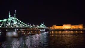 Βάρκες κάτω από τη γέφυρα ελευθερίας που φωτίζεται τη νύχτα απόθεμα βίντεο