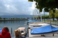 Βάρκες πανιών στα ρυμουλκά, το λιμενοβραχίονα Rapperswil, τα σύννεφα και τους λόφους στον ορίζοντα Στοκ Φωτογραφία