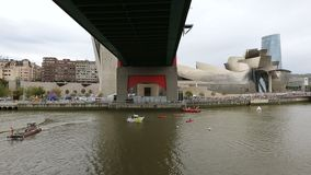 Βάρκες που πλέουν κάτω από τη γέφυρα καταπραϋντικών Λα, προετοιμασία για τον ανταγωνισμό, Μπιλμπάο, Ισπανία φιλμ μικρού μήκους