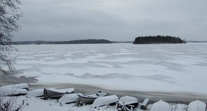 Βάρκες στην παραλία της παγωμένης λίμνης στοκ εικόνα