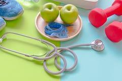 Βάρος αδυνατίσματος διατροφής με το πράσινο μήλο και τη μέτρηση της βρύσης, βάρος κλίμακας, αλτήρες, ζωηρόχρωμο υπόβαθρο Στοκ Φωτογραφία
