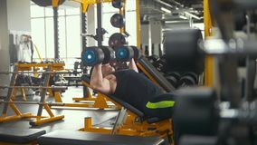 Βάρος-ανύψωση στη γυμναστική - ο μυϊκός αθλητής εκτελεί την κατάρτιση για τους δικέφαλους μυς με τους αλτήρες φιλμ μικρού μήκους